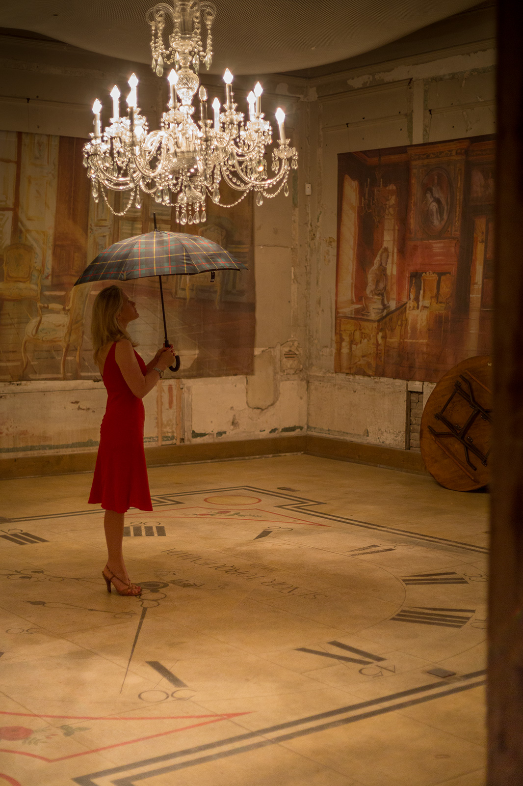Woman with umbrella under chandelier